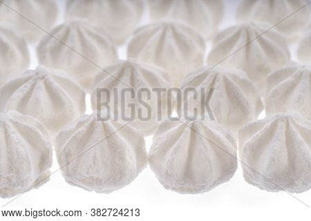 Background From White Meringue Cookies. Sweet Crispy Twisted Cooked Meringue. Whipped Egg Cream Cook