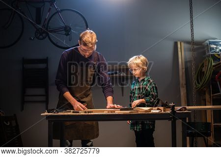 A Young Male Carpenter Is Teaching Woodwork To A Young Boy In His Workshop