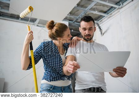 A Man And A Woman Are Smiling And Looking At The Work Plan During The Renovation Of An House
