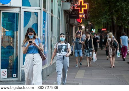 Belgrade, Serbia - July 28, 2020: Two Young Women Wearing A Respiratory Face Mask Checking Apps On T