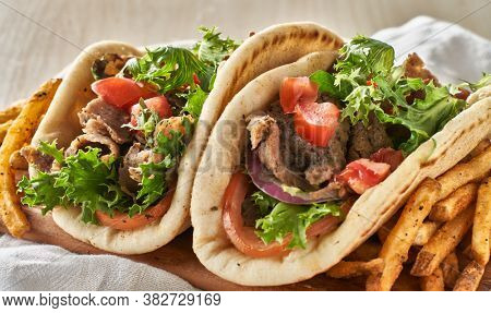 two greek gyros with fries, tomato and lettuce