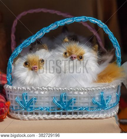 Two Little Fluffy Creatures In A Blue Wicker Basket On The Souvenir Counter.  The Sun Shines Brightl