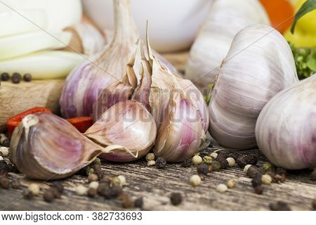 Cloves Of Ripe Garlic On The Kitchen Table While Cooking A Dish With Garlic, Sliced Garlic On A Cutt