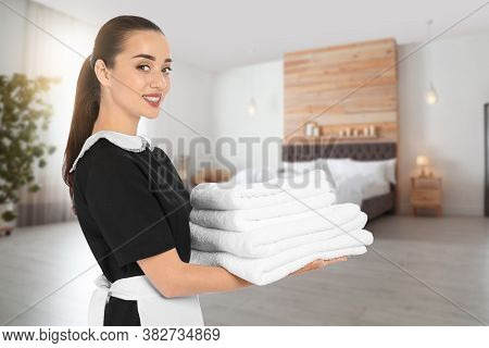 Beautiful Chambermaid With Clean Folded Towels In Hotel Room