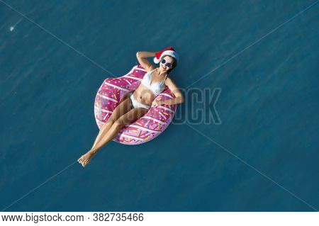 Young Woman Wearing Santa Hat And Bikini With Inflatable Ring In Sea, Top View. Christmas Vacation