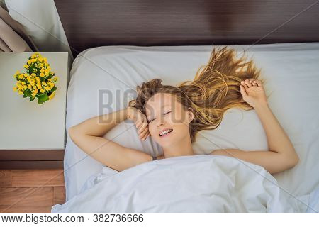 Sleep Without A Pillow. Young Woman Sleeping In Bed Without A Pillow. Portrait Of Beautiful Female R