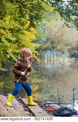 Little Boy Fishing. Kid Pulling Rod While Fishing On Weekend