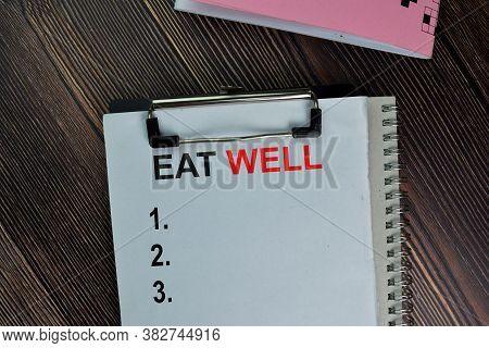 Eat Well Write On A Paperwork. Supported By An Additional Services Isolated On Wooden Table.