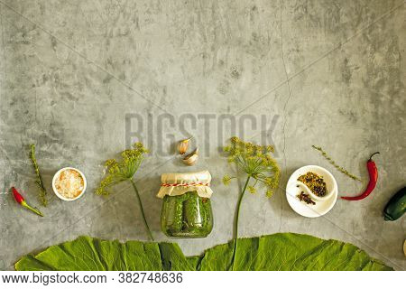 Pickled Cucumbers In A Jar Background Frame Copy Space. Jar With Canned Cucumbers, Fresh Herbs, Pepp