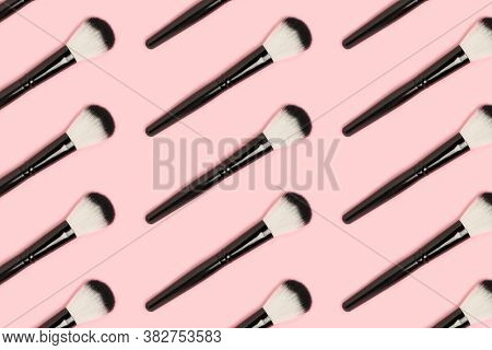 Repetitive Pattern Made Of Black Makeup Brushes On A Pink Background. Beauty Backdrop.