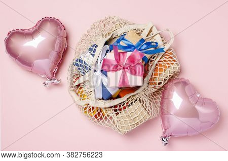 Shopping Bag With Gift And Heart Shaped Air Balloon On A Pink Background. Gifts Concept For Family,