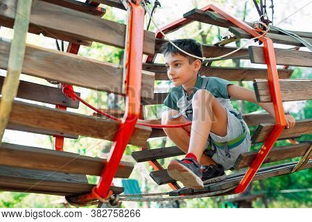 Rope Park. The Kid Passes The Obstacle In The Rope Park.