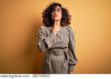 Beautiful arab business woman wearing dress and glasses standing over yellow background Thinking concentrated about doubt with finger on chin and looking up wondering