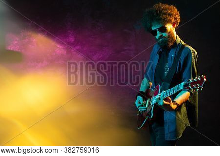 Stylish Hipster Man With Red Guitar In Neon Lights. Rock Musician Is Playing Electrical Guitar.