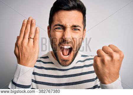Handsome man with beard showing alliance ring marriage on finger over white background annoyed and frustrated shouting with anger, crazy and yelling with raised hand, anger concept