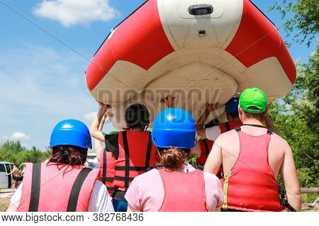 Rafting Team In Sports Equipment After A Successful Rafting Along The River Carry A Rubber Inflatabl