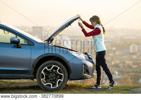 Young Woman Opening Bonnet Of Broken Down Car Having Trouble With Her Vehicle. Female Driver Standin