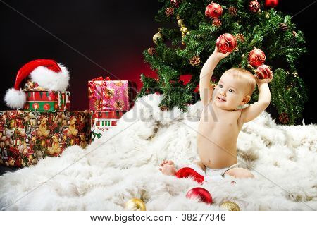Christmas Baby Sitting On Fur Holding Red Ball Near New Year Fir Tree And Gift Box