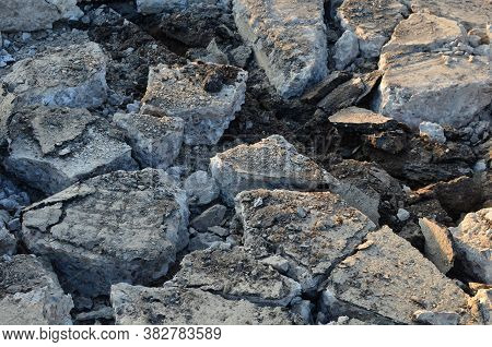Broken Pieces Of Asphalt At A Construction Site. Recycling And Reuse Crushed Concrete Rubble, Asphal