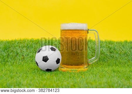 Big Mug Filled With Cold Beer With Foam, And Miniature Soccer Ball Stand On Grass Of Artificial Lawn