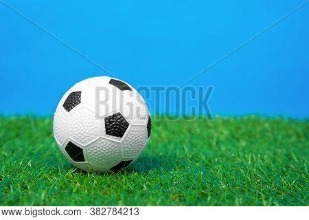 Miniature Toy Soccer Ball Lies On Green Grass Of Artificial Turf Of Football Field, Blue Background,