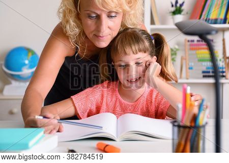 Mother Helping Her Daughter To Study  On Study Table With Teaching Items At Home