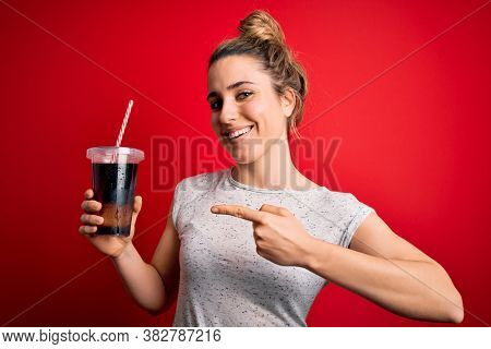 Beautiful blonde woman drinking cola fizzy beverage to refreshment over red background very happy pointing with hand and finger