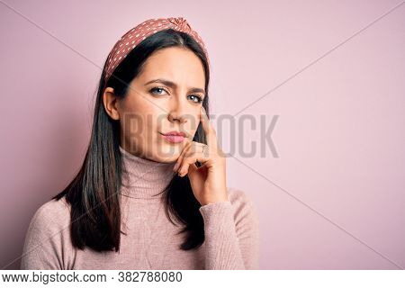 Young brunette woman with blue eyes wearing casual t-shirt and diadem with hand on chin thinking about question, pensive expression. Smiling with thoughtful face. Doubt concept.