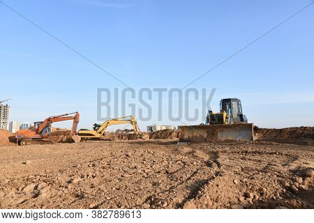 Excavators And Dozer Digs Ground At A Construction Site For Installing Sewer Storm Pipes. Backhoe Fo