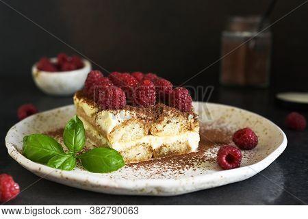 Tiramisu With Raspberries On A Dark Concrete Background. The Classic Italian Dessert Is Tiramisu.