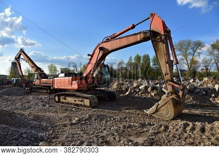 Excavator And High Reach Machines For Demolition Of Tall Building. Machine With Hydraulic Shears For
