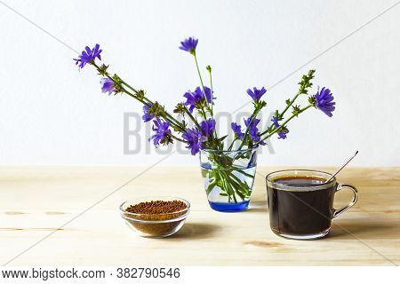A Cup Of Chicory, Granules Of Freeze-dried Instant Chicory And Blue Flowers On A Light Wooden Backgr