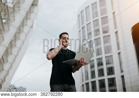 Young Handsome Brunette Man Walking Down The Street, Working In His Laptop And Eating Sandwich On Th