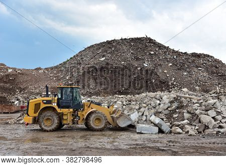 Front End Loader At Landfill For Disposal Of Construction Waste. Backhoe Digs Gravel And Concrete Cr