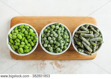 Frozen Vegetables Such As Green Peas, Soy, Green Beans And Baby In White Bowls Top View. Healthy Foo