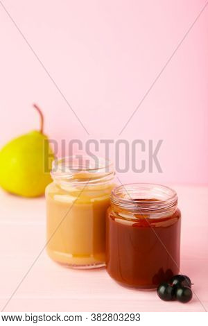 Glass Jars With Nutrient Baby Food On Pink Background. Vegetable And Fruit Puree. Vertical Foto