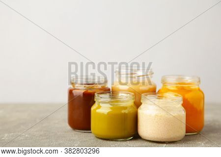 Glass Jars With Nutrient Baby Food On Light Background. Vegetable Puree With Spoon.