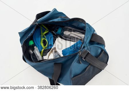 Swimming Gear Set. Top View Of Sports Bag With Swim Goggles, Hat Or Cap, Towel And Bottle Of Water I