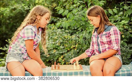 Think Better. Children Play Chess Outdoors Nature Background. Sport And Hobby Concept. Little Girls