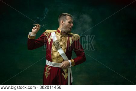 Disguasted Smoking Cigarette. Young Man In Suit As Nicholas Ii On Dark Green Background. Retro Style