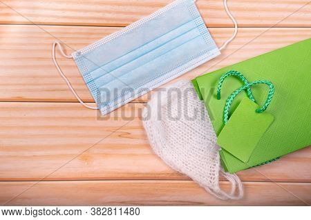 Face Mask And  Newborn's Hat On Gift Bag Over Wood Background. Pregnancy And Baptism Concept. Social