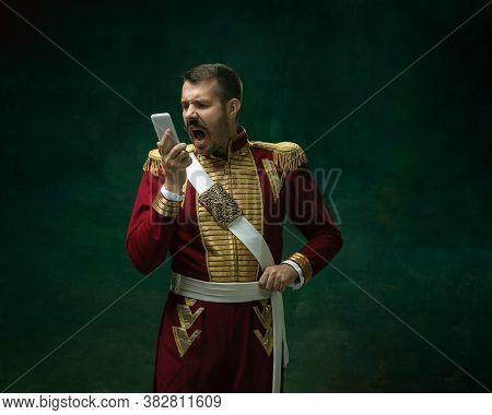 Screaming On Phone. Young Man In Suit As Nicholas Ii On Dark Green Background. Retro Style, Comparis