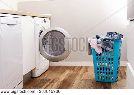 Open Washing Machine And Laundry Basket. Concept Doing The Laundry In The Kitchen