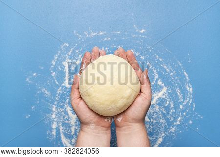 Woman Holding Dough In Hand Over A Blue Background. Top View Of Uncooked Dough. Baking At Home Conce