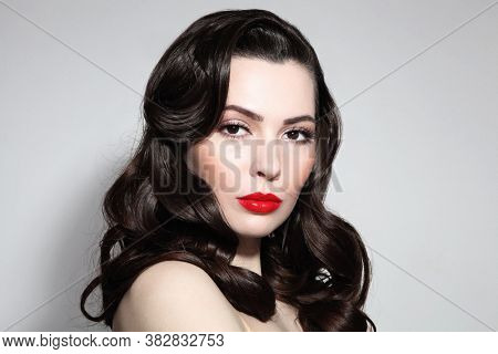 Young beautiful brunette with long curly hair and red lipstick
