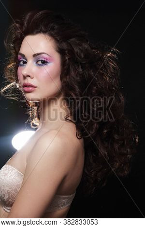 Vintage style portrait of young beautiful woman with long curly hair and fancy disco makeup