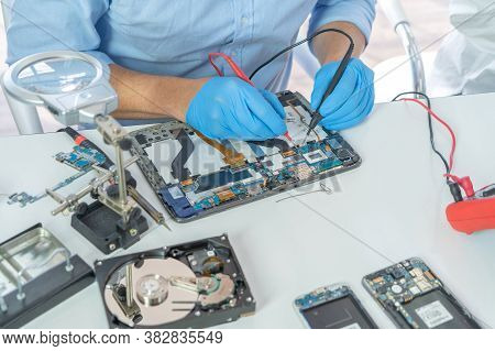 An Engineer Or Technician Western Man Working, Examining Or Repairing Computer Motherboard Equipment