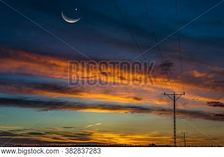 Sunset Above The Field And A New Moon Into The Sky