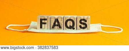 Faqs Word Written On Wood Block. Faqs Text On Table, Concept. Yellow Background.