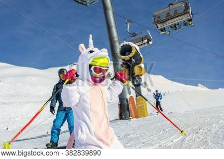 Cute Adorable Preschooler Caucasian Kid Girl Portrait With Ski In Helmet, Goggles And Unicorn Fun Co